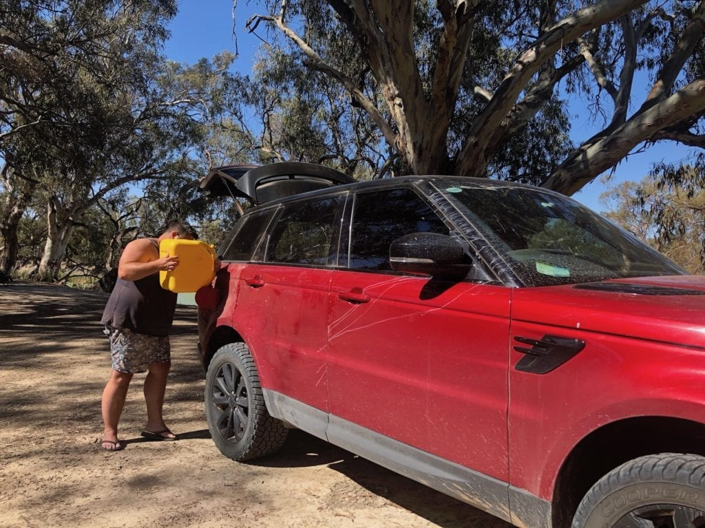 Emptying a jerry can into the Range Rover Sport.