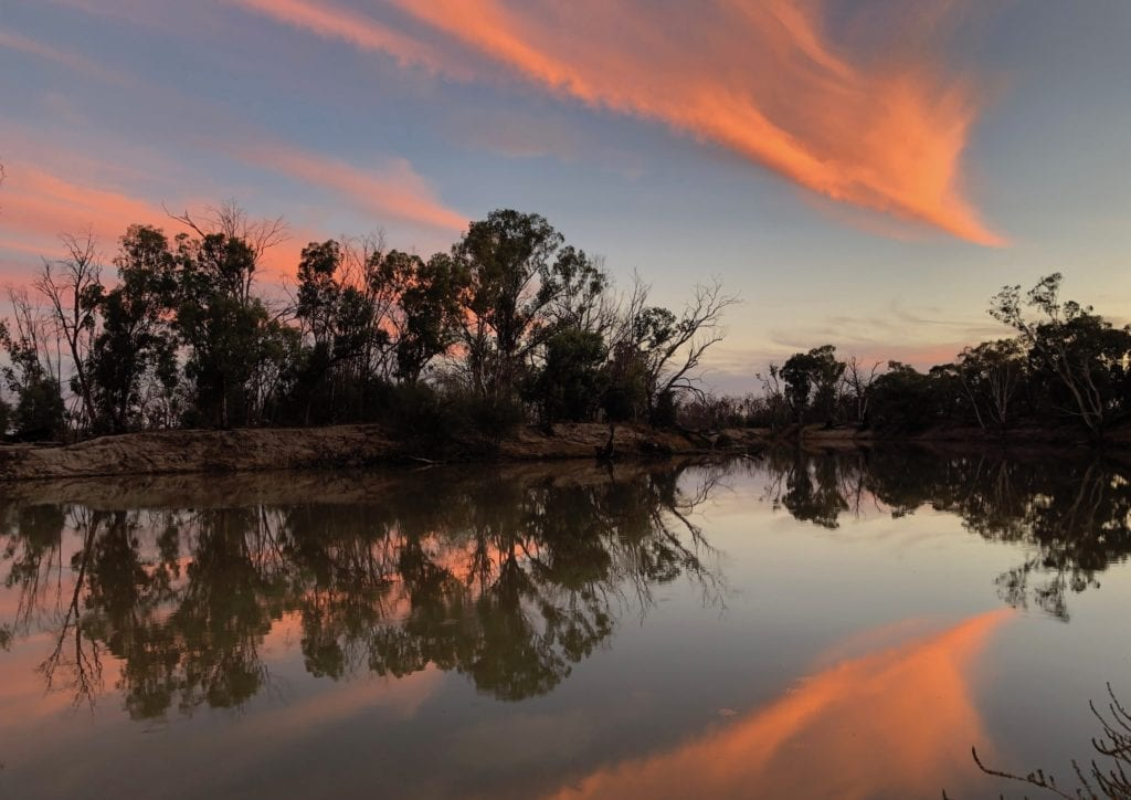 Camping On The Murray River. Bright orange clouds reflecting off the river.